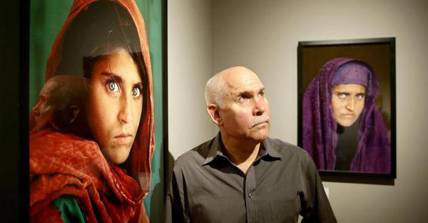 epa03762741 US photographer Steve McCurry stands amongst his pictures in the exhibition 'Steve McCurry. Overwhelmed by Life' at the Museum of Arts and Crafts in Hamburg, Germany, 27 June 2013. The museum shows about 120 photographs by the Magnum photographer with pictures from countries such as Pakistan, Kuwait, and Tibet until 29 September.  EPA/ULRICH PERREY