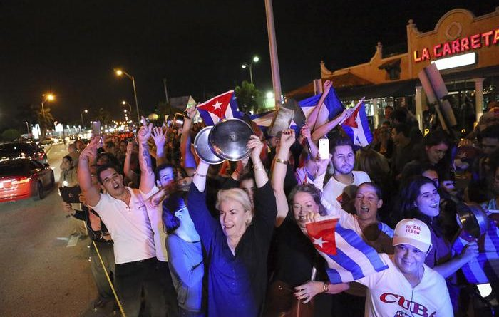 The Cuban community celebrates the announcement that Fidel Castro died in front La Carreta Restaurant, early Saturday, Nov. 26, 2016, in Miami. Within half an hour of the Cuban governments official announcement that former President Fidel Castro had died, Friday, Nov. 25, 2016, at age 90, Miamis Little Havana teemed with life - and cheers.  (David Santiago/El Nuevo Herald via AP)